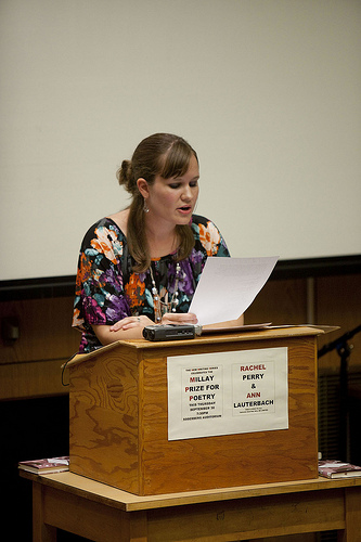 Person standing at lectern, reading from sheet of paper