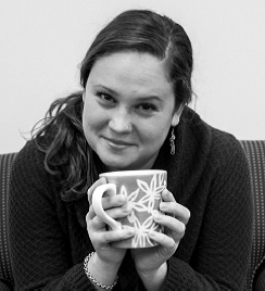 Headshot of woman smiling at camera, drinking out of mug