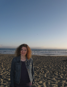 Half-body shot of woman looking at camera, on beach in front of ocean