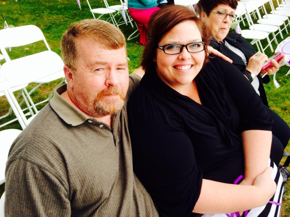 Man and woman smiling at camera, in audience outdoors