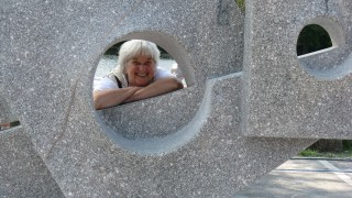 Woman smiling at camera, looking through gap in concrete sculpture