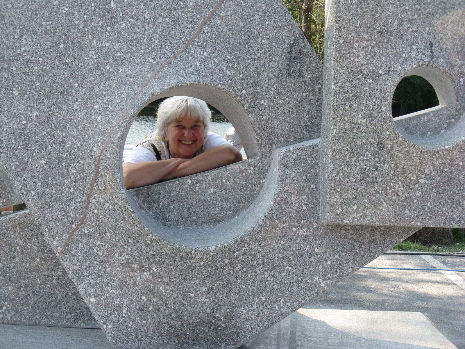 Judith smiling at camera, looking through gap in concrete sculpture