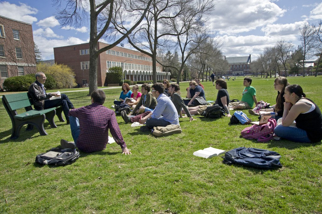 Students seated on lawn on sunny day listening to a professor speak