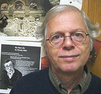 Headshot of man smiling at camera in front of Woody Allen poster