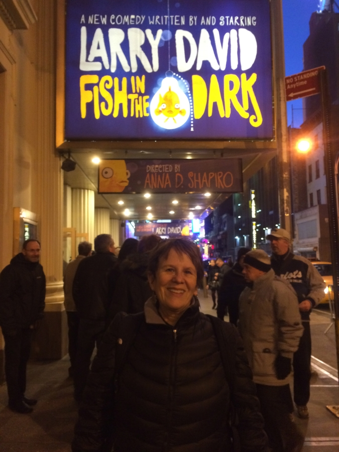 "Smiling woman standing in front of a crowd on a city street; marquee overhead reading ""A NEW COMEDY WRITTEN BY AND STARRING LARRY DAVID; FISH IN THE DARK; DIRECTED BY ANNA D. SHAPIRO"""