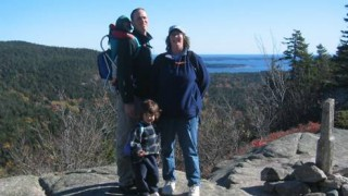 Woman, man, and small child standing on top of a mountain overlooking the coast