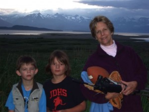 Woman and two children standing in front of flat marshland, with water and mountains behind