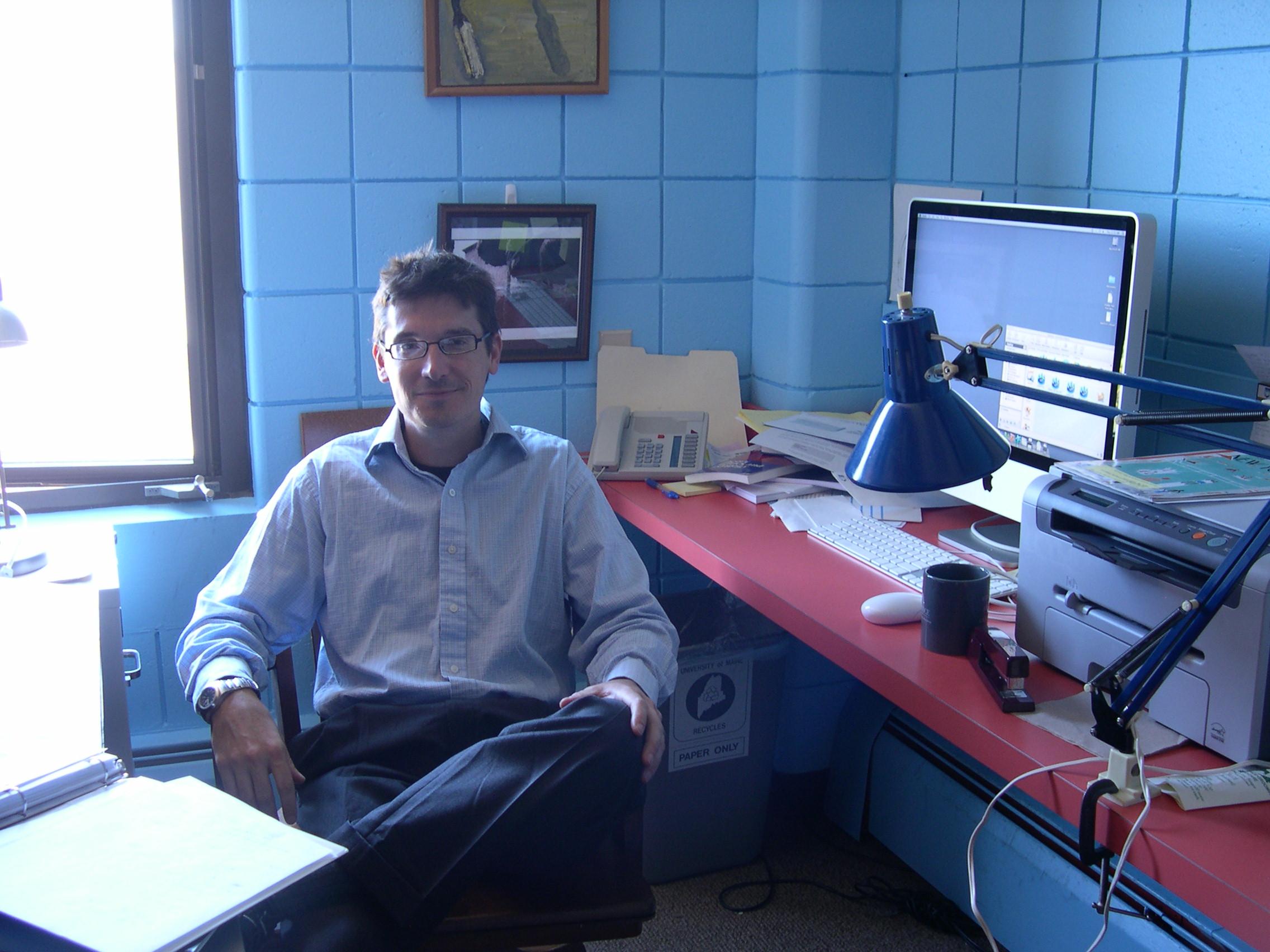 Man seated at desk, smiling at camera