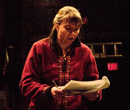 Half-body shot of woman reading from a document on a darkened stage