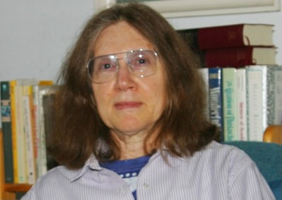 Headshot of person with long hair and glasses looking at the camera, seated in front of a row of books.