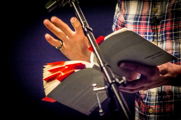 new writing series picture of speaker holding book and gesturing with hand in front of a mic