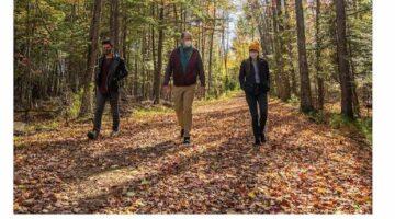 Three humans walk on a leafy path.
